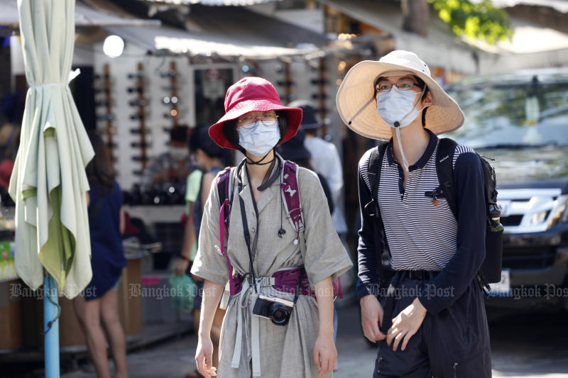Foreign tourists wear face masks to protect themselves from coronavirus or Covid-19 as they take a walk around Chatuchak weekend market on Feb 15, 2020.  (Photo by Nutthawat Wicheanbut)