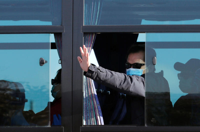 A passenger waves from a bus transporting Hong Kong passengers from the coronavirus-hit cruise ship Diamond Princess, as they leave the Daikoku Pier Cruise Terminal in Yokohama on Feb 21, 2020. (Reuters photo)