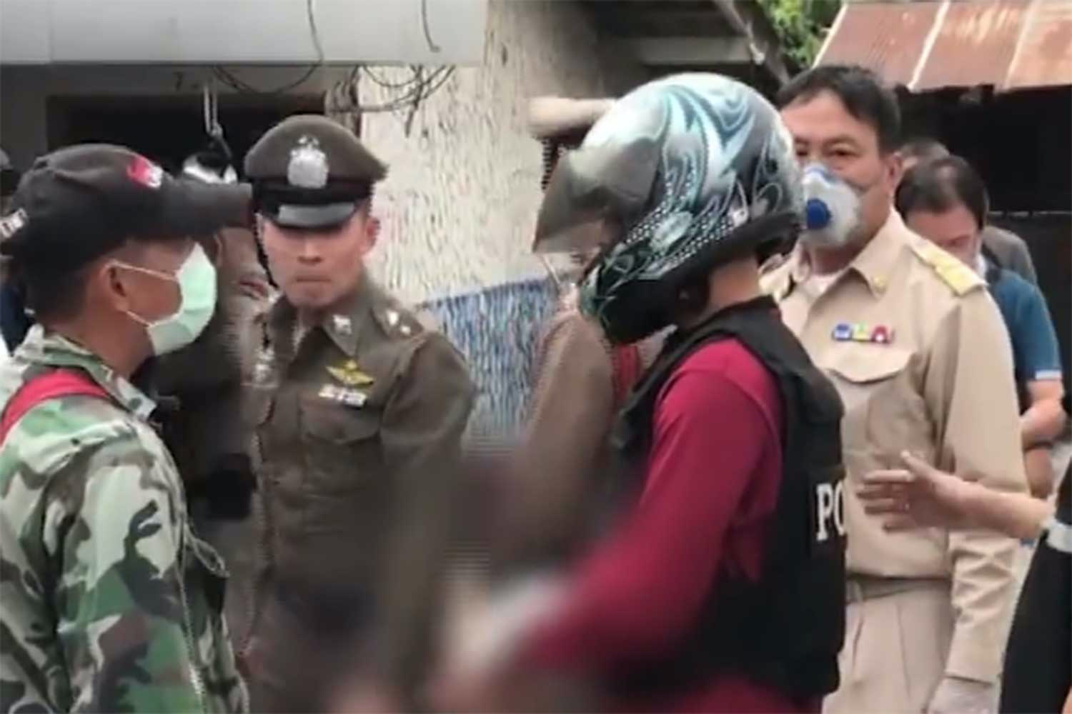 An image from a TV Channel One shows the suspect being taken for a re-enactment of his mother's murder at his home in Hua Wiang village in Wiang Pa Pao district of Chiang Rai on Friday.