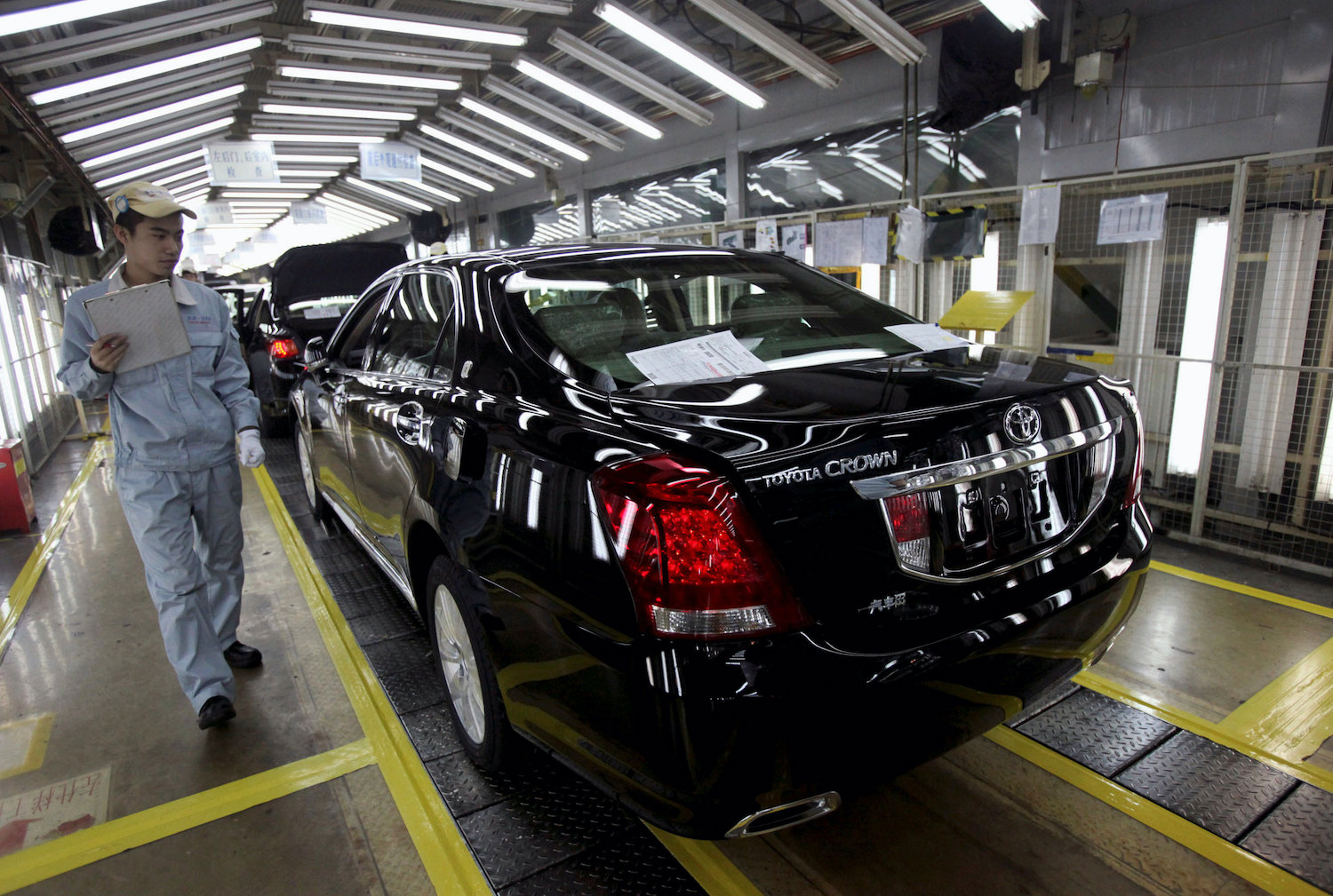 An employee inspects a new Toyota Crown at the Japanese carmaker's plant in Tianjin, China. (Reuters Photo)