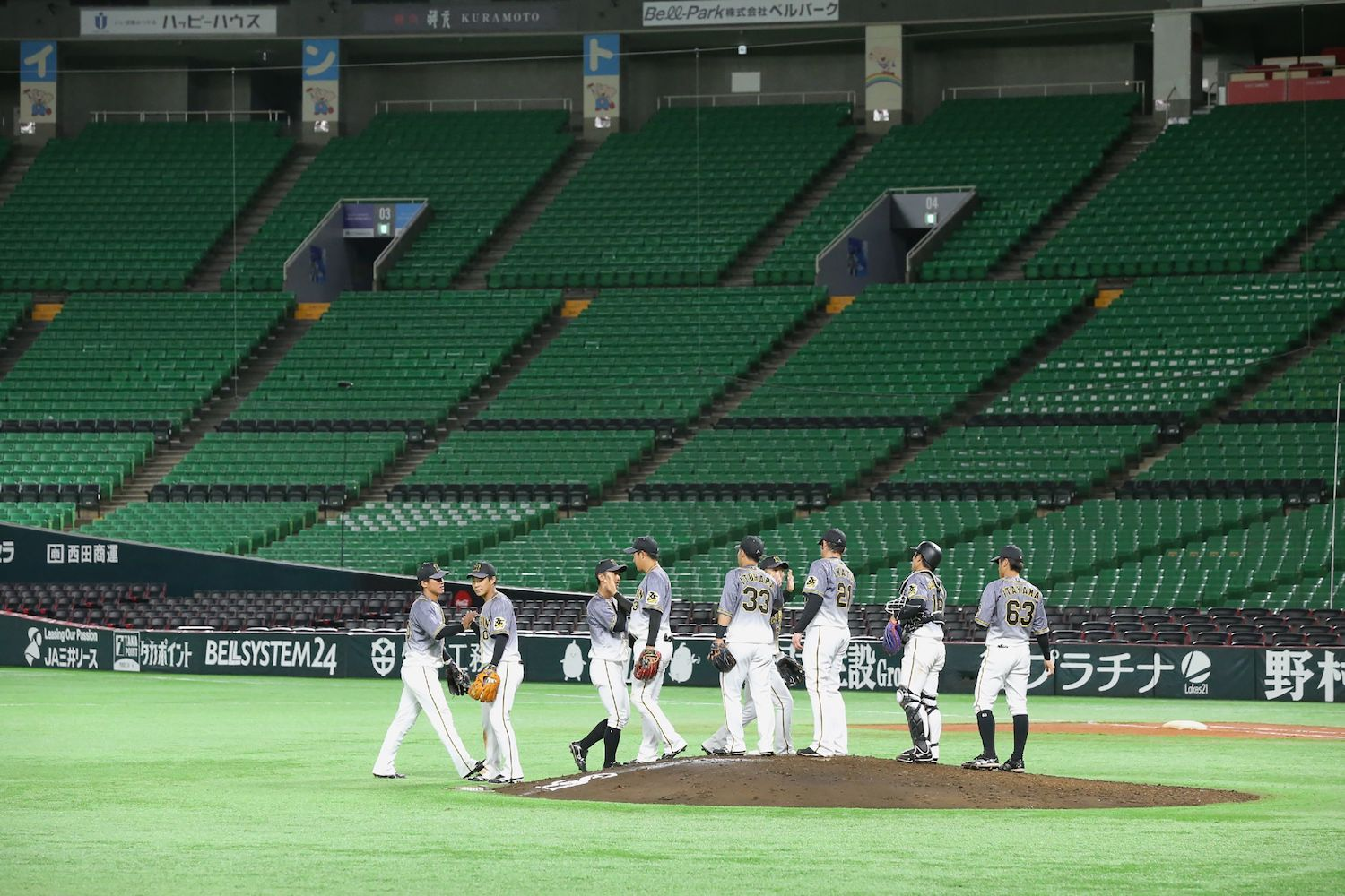 Hanshin Tigers players celebrate their win over Fukuoka SoftBank Hawks following their pre-season game in an empty stadium in Fukuoka on Saturday. (Jiji Press via AFP)