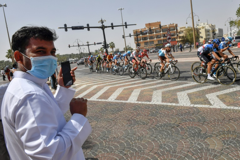 A man wearing a surgical mask looks on as the peleton rode by on Thursday's stage five