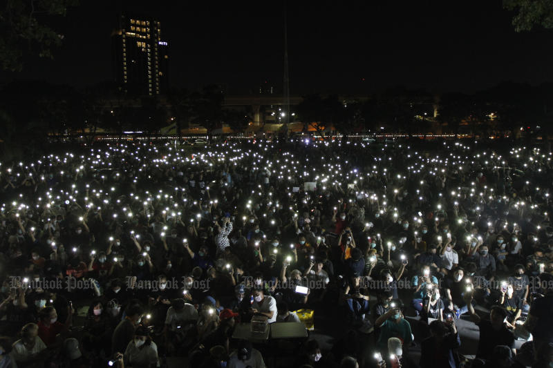 Students light their mobile phones during a protest agaisnt the government at Kasetsart University on Saturday. (Photo by Wichan Charoenkiatpakul)