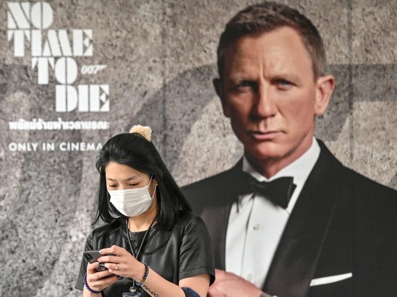 A woman wearing a facemask amid fears of the spread of the Covid-19 novel coronavirus walks past a poster for the new James Bond movie