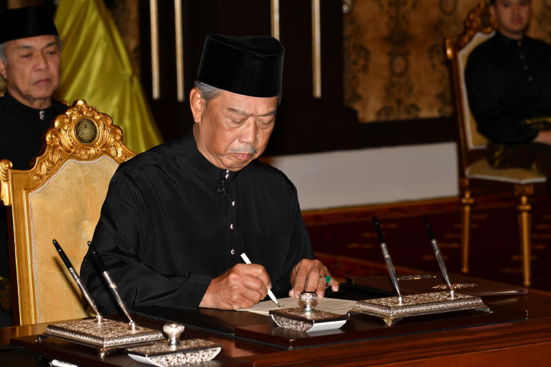 Muhyiddin Yassin signs a document during swearing-in ceremony as Malaysia's prime minister in Kuala Lumpur, Malaysia, on Sunday. (Malaysia Information Department/Famer Roheni/Handout via Reuters)