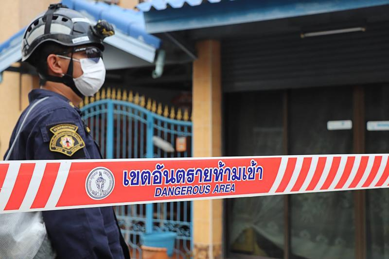 FILE PHOTO: A local security guard wearing a protective face mask stands outside a house after family members were infected with Covid-19 coronavirus in Bangkok, on Feb 27, 2020.