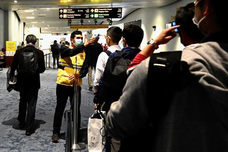 FILE PHOTO: An Indonesian health officials takes temperature readings of arriving passengers amid concerns of the Covid-19 coronavirus at the Jakarta international Airport on Feb 23, 2020. (AFP)