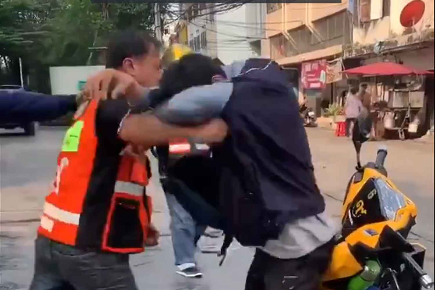 A screenshot from the video of Facebook user Amittaa Phongsawat shows a taxi motorcyclist attacking a Grab motorcyclist on Sukhumvit 48 Road in Klong Toey district of Bangkok on Monday morning.