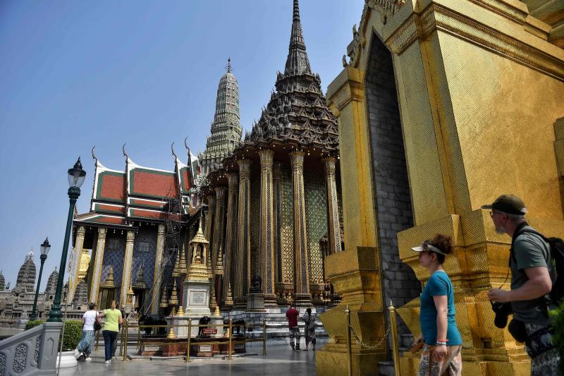 Tourists walk through an unusually empty Grand Palace in Bangkok on Monday. (AFP photo)