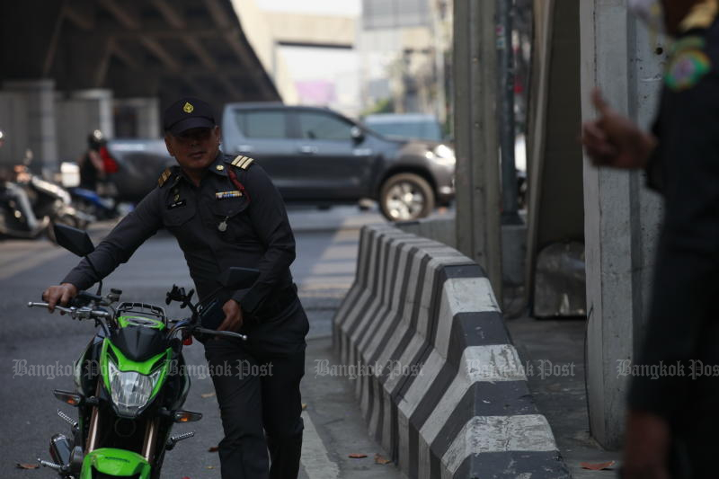 A Thetsakit official seizes a motorcycle parked on pavements in Chatuchak district on Feb 20, 2020. (Photo by Nutthawat Wicheanbut)