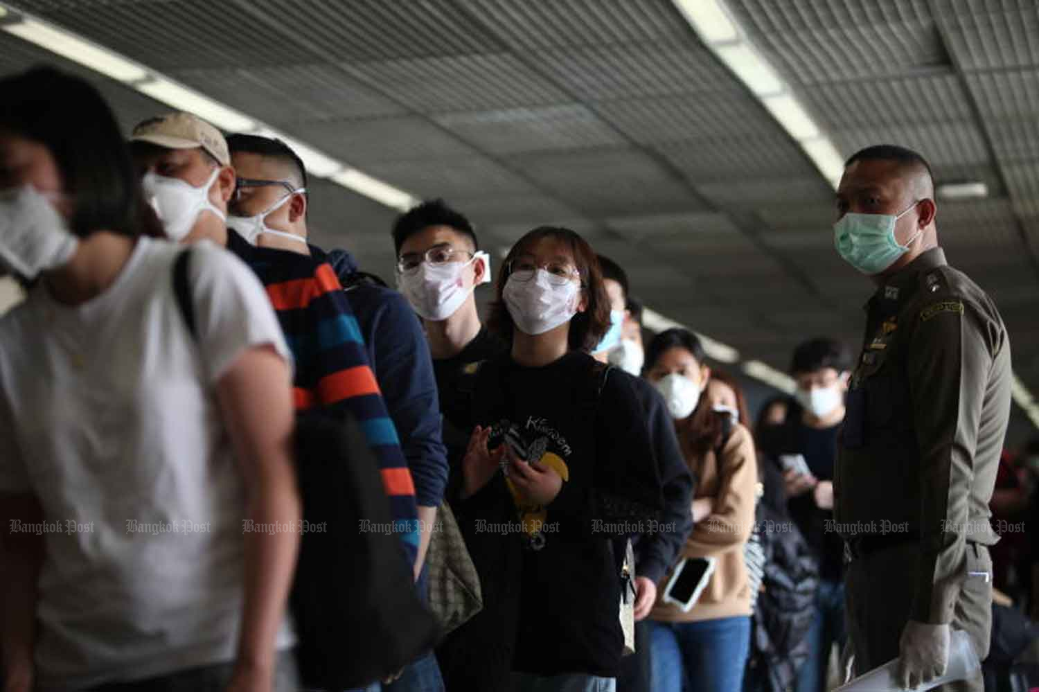 Passengers arriving from China stand in a long queue as they wait to walk through a thermal scanner at Don Mueang Airport late in January. (File photo by Apichart Jinakul)