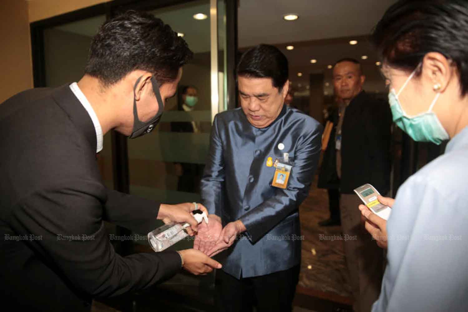 Industry Minister Suriya Jungrungreangkit takes a squirt of sanitising gel and has his temperature taken as part of measures at Government House to combat the Covid-19 outbreak. (Photo by Chanat Katanyu)