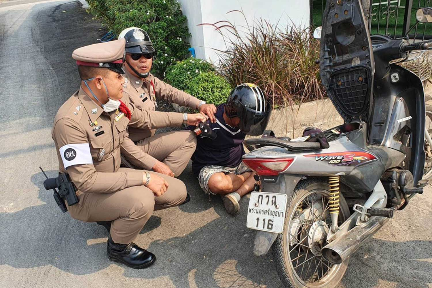 Police hold Somkhid Ruennangyaem after finding an registered pistol and ammunition in his possession, in Phra Nakhon Si Ayutthaya district of Ayutthaya province on Tuesday. He allegedly confessed he planned to shoot his wife and her lover at a shopping mall. (Photo  via Sunthorn Pongpao)