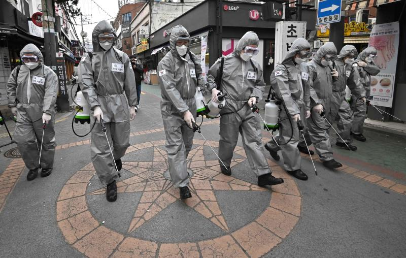 South Korean soldiers wearing protective gear spray disinfectant to help prevent the spread of the Covid-19 coronavirus, at a shopping district in Seoul on Wednesday. (AFP photo)