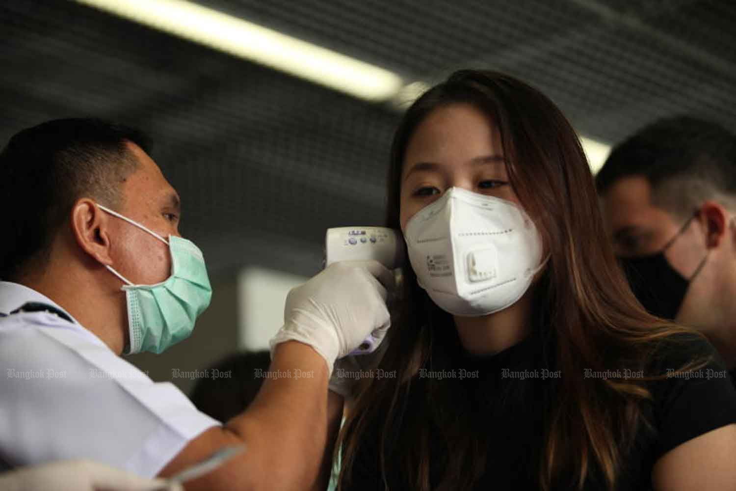 An official checks the temperatures of passengers at Don Mueang Airport in Bangkok. The government has decided to quarantine Thai workers returning from a Covid-19-affected province of South Korea. (Photo: Apichart Jinakul)