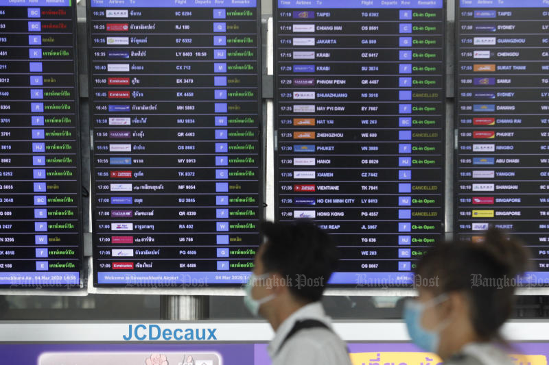 Passengers walk past a panel showing outbound flight information at Suvarnabhumi airport on Wednesday. (Photo by Wichan Charoenkiatpakul)