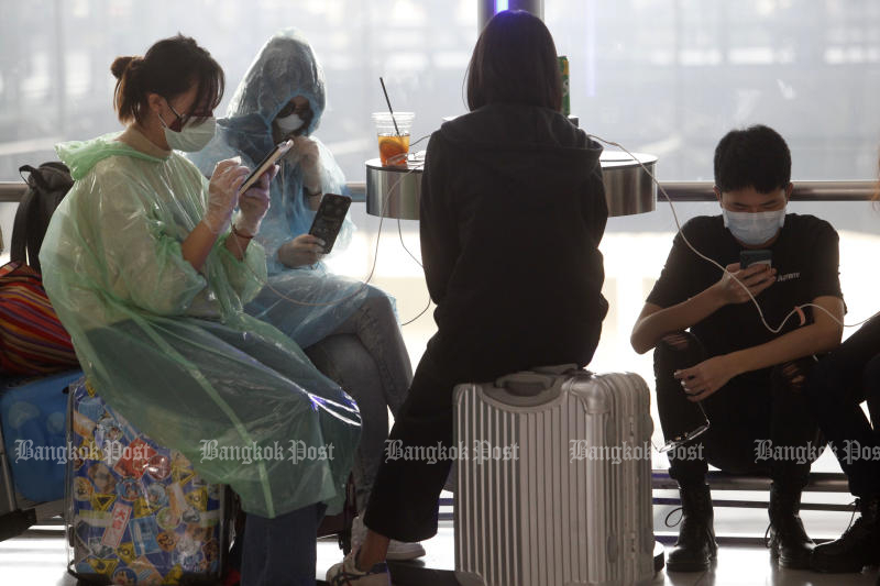 Tourists wear protective masks and other gears at Suvarnabhumi airport on Wednesday. (Photo by Wichan Charoenkiatpakul)