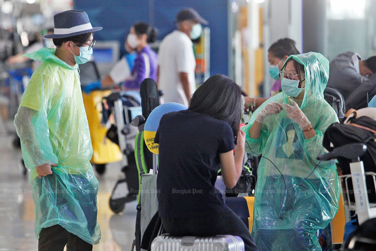 Foreign travellers at Suvarnabhumi airport wear face masks and green plastic anoraks to protect themselves from Covid-19 as aviation agencies seek to step up the screening of passengers from countries suffering epidemics of the virus. (Photo by Wichan Charoenkiatpakul)