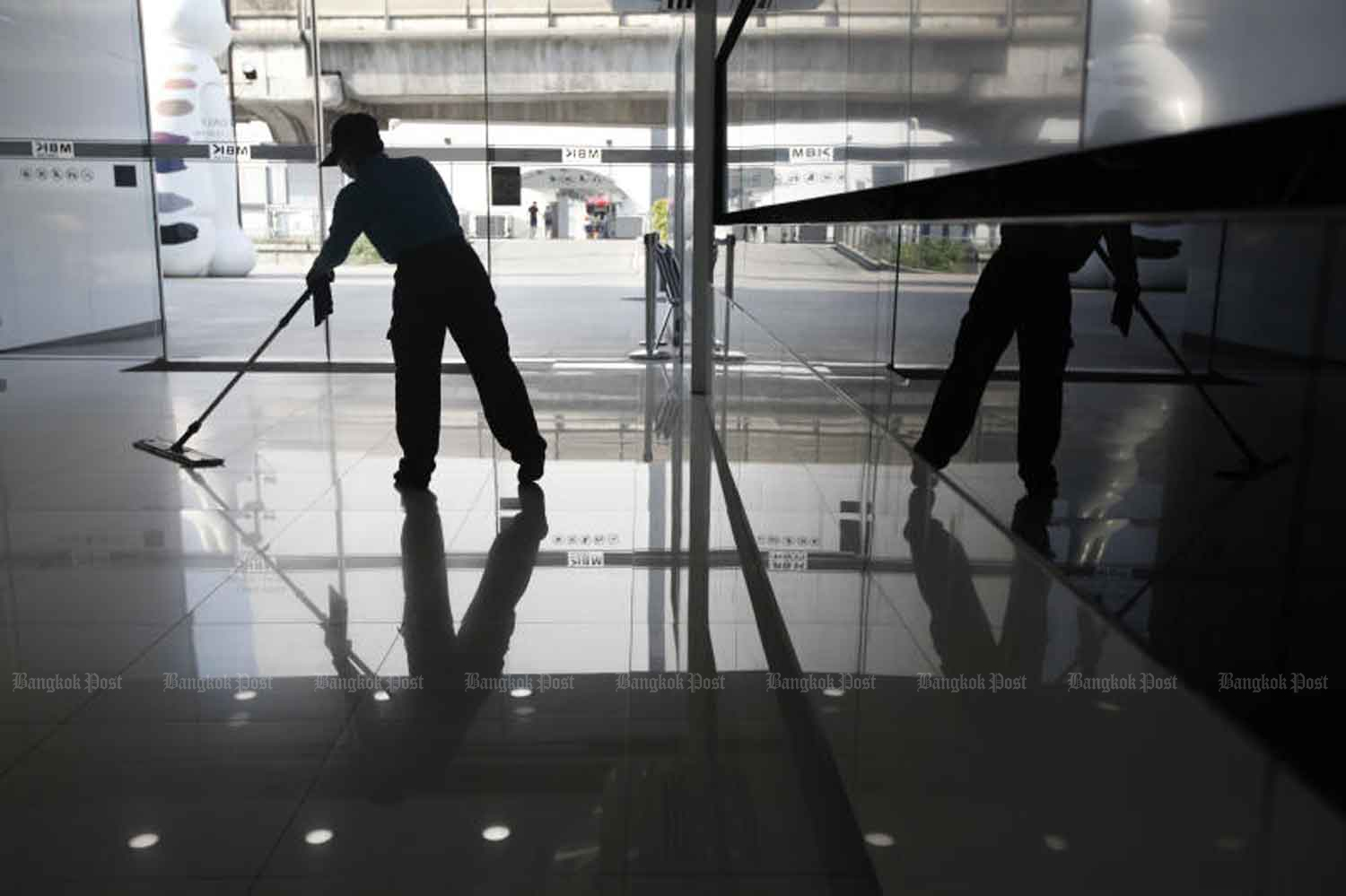 A cleaner is at work at the MBK shopping centre in Pathumwan district of Bangkok. The obvious disappearance of tourists causes Kasikorn Research Center to predict a meagre economic growth this year. (Photo by Wichan Charoenkiatpakul)