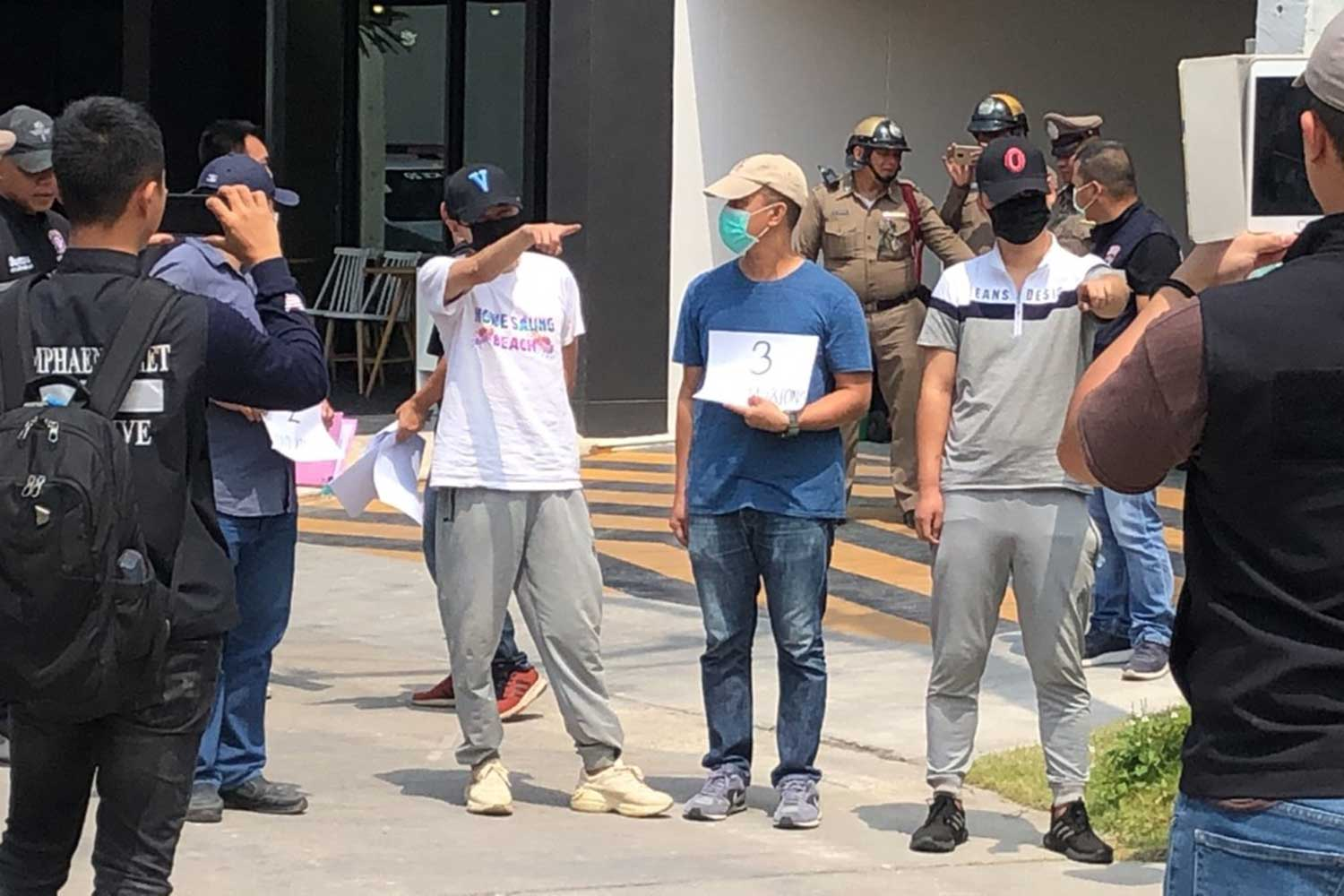 Fan Gang Gang, 24, and Qin Miao, 31, both wearing black face masks, are taken for crime re-enactment at a house in Pattaya. (Photo by Chaiyot Pupattanapong)