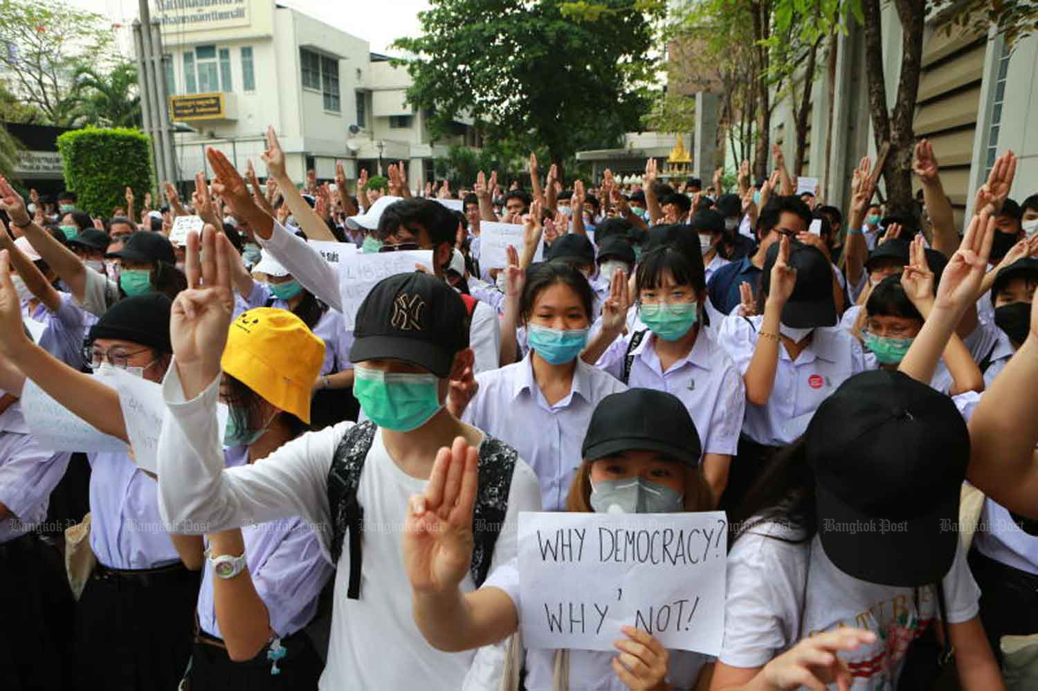 Students hold up the three-finger salute as they denounce dictatorship and stand up for democracy at Triam Udom Suksa School in Bangkok on Feb 27. (Photo: Somchai Poomlard)