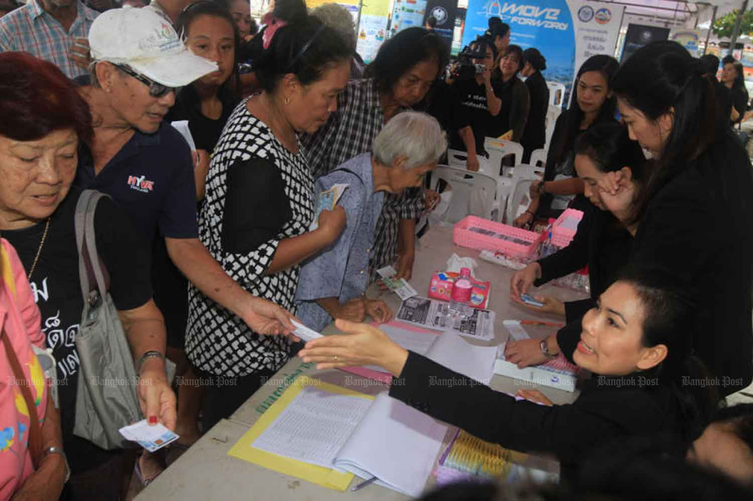 Officials hand out government welfare cards to registered poor people at the provincial hall of Samut Prakan in 2017. (Photo: Somchai Poomlard)