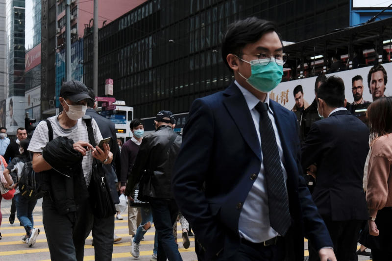 People wear protective face masks as they take their lunch breaks at the financial Central district following the outbreak of the new coronavirus in Hong Kong on Monday. (Reuters photo)