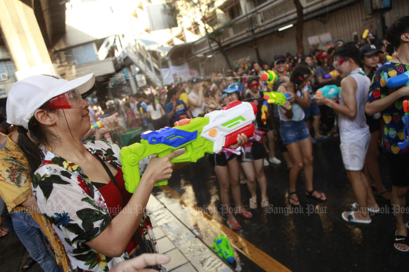 People enjoy water splashing during the Songkran festival on Silom Road in Bangkok last year. Will they be back this year? (Photo by Pornprom Satrabhaya)