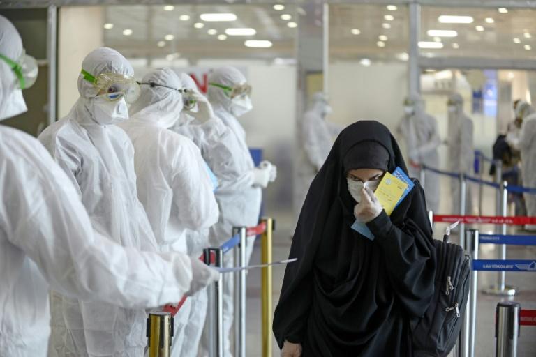 Medical staff distribute information sheets to Iraqi passengers returning from Iran at Najaf International Airport.
