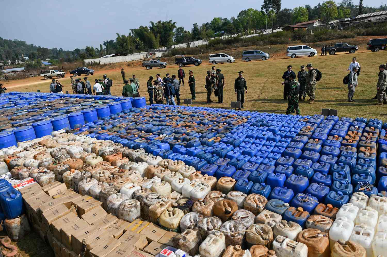 Foreign military attachés gather on a football ground where seized drugs, vehicles, laboratory accessories and precursor chemicals were displayed in Kawnghka at Shan State on Friday. (AFP Photo)