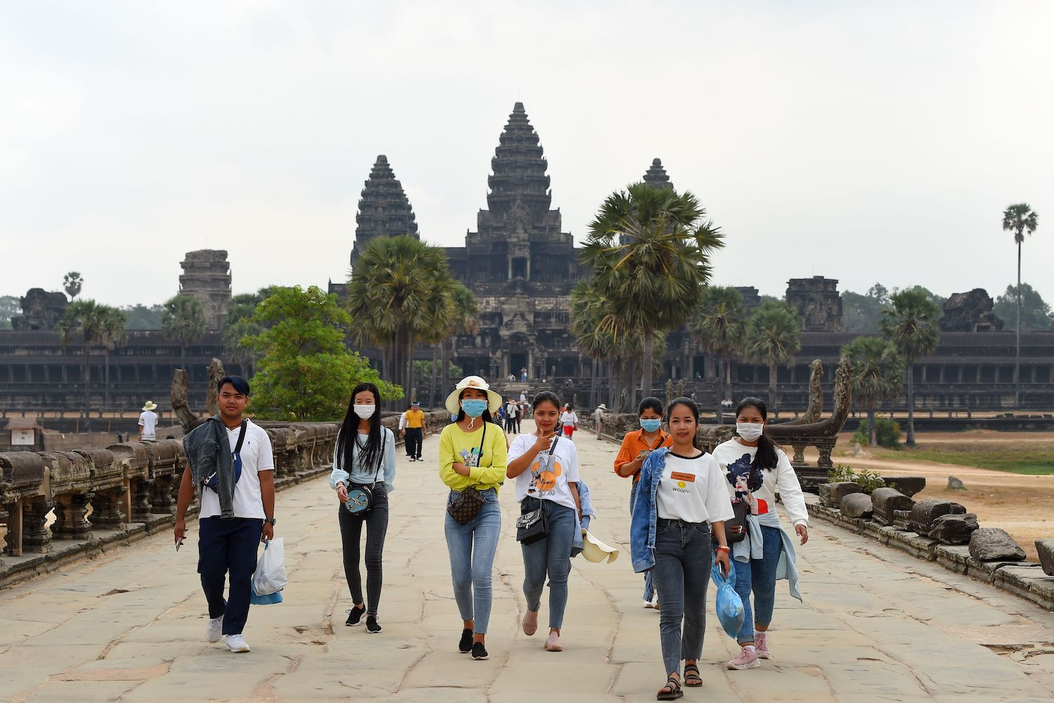 People wear face masks as they visit Angkor Wat in Siem Reap province of Cambodia on Friday. (AFP Photo)