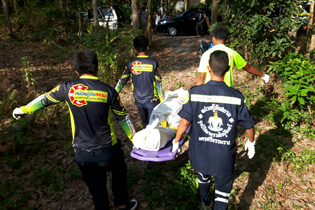 Rescue volunteers take the body of hit man Yuthana Chukaew to a hospital for an autopsy after he died from an unspecified illness at his house in Ron Phibun district of Nakhon Si Thammarat on Sunday. (Photo by Nujaree Raekrun)