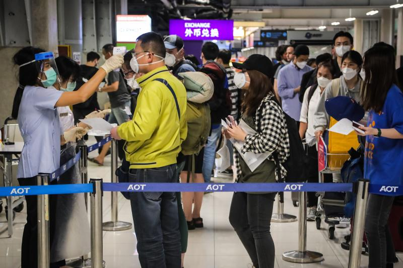 A health official checks the temperature of an incoming passenger during a health assessment at a checkpoint for people flying in from a list of countries and territories that include China, Hong Kong, Macau, South Korea, Iran and Italy, as a precautionary measure against the spread of the Covid-19 coronavirus at Suvarnabhumi Airport in Bangkok on Monday. (AFP photo)