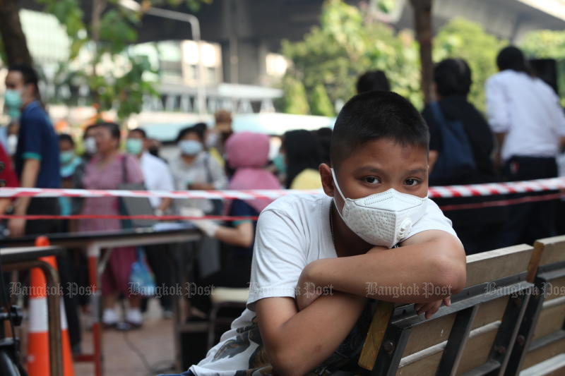 A boy waits while his family inches forward in a long line to buy protective masks at a chemist operated by the Government Pharmaceutical Organisation on Monday. (Photo by Apichart Jinakul)