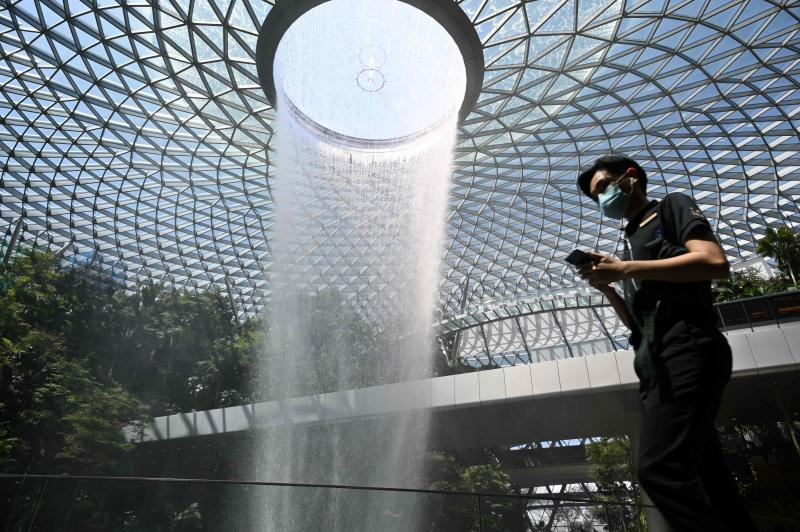 A man, wearing a protective facemask amid fears about the spread of the Covid-19 novel coronavirus, walks past the Rain Vortex display at Jewel Changi Airport in Singapore on Feb 27, 2020. (AFP photo)