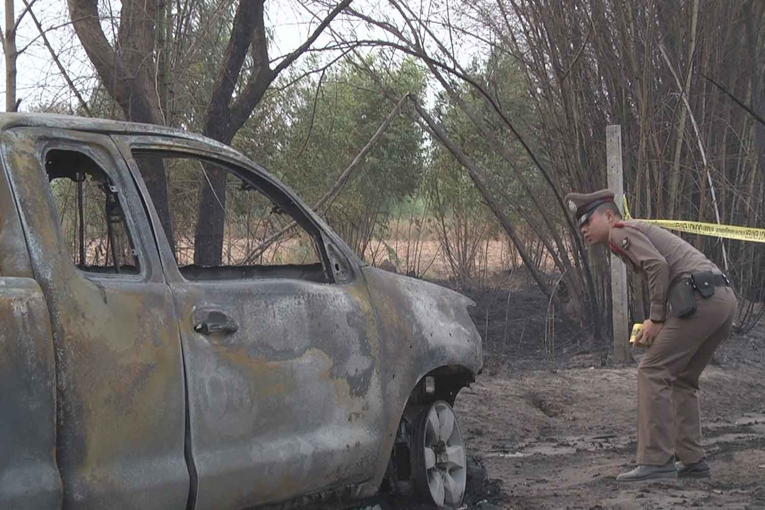 A police officer examines the burned-out pickup in which the charred body of a man was found, at a cassava plantation in Muang district of Nakhon Ratchasima on Tuesday. (Photo: Prasit Tangprasert)