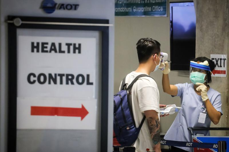 A health official checks the temperature of an incoming passenger during a health assessment at a checkpoint at Suvarnabhumi airport on Monday. (AFP photo)