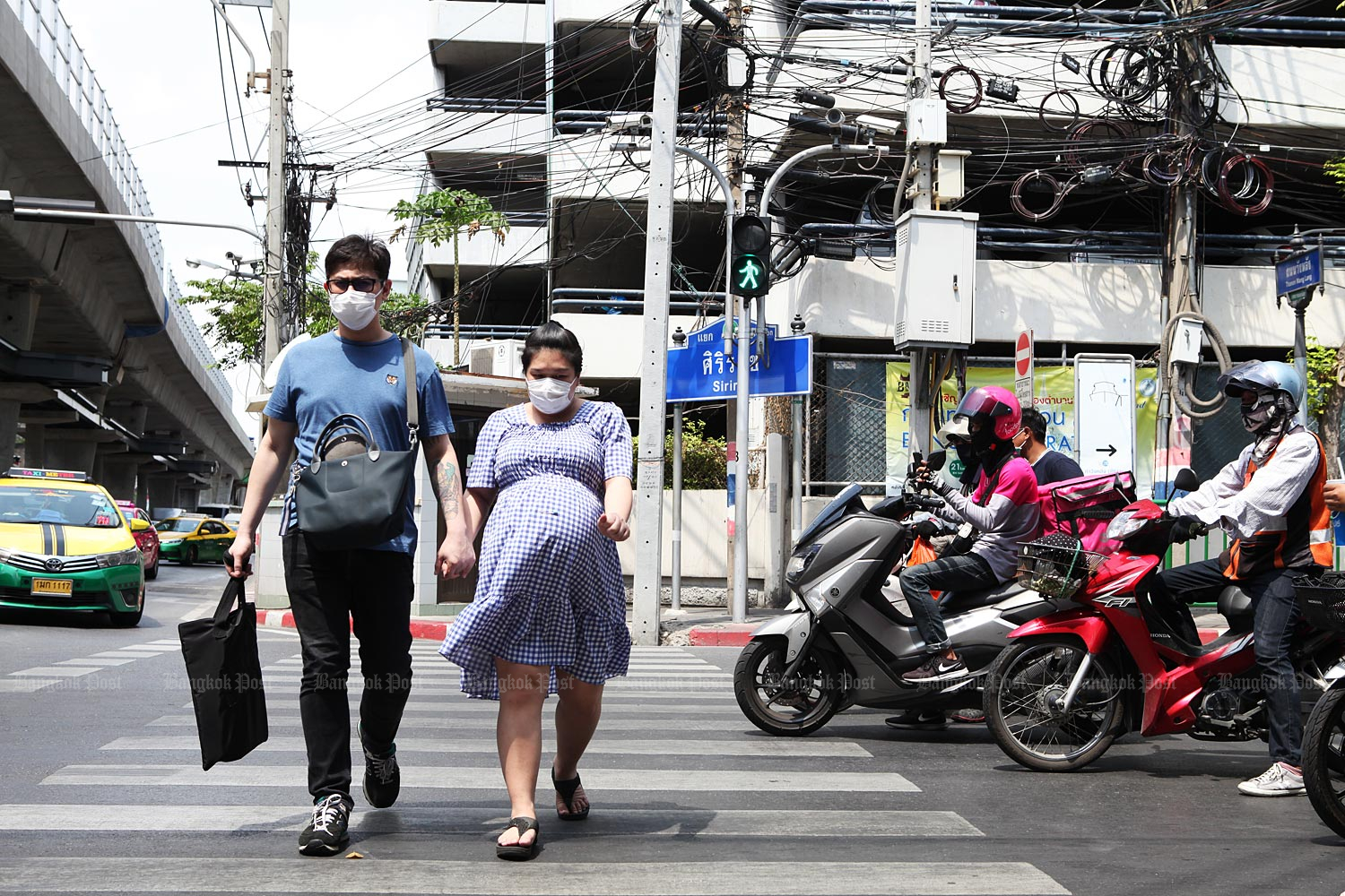 Masking a crisis: A couple wearing face masks cross the road at a busy intersection near Siriraj Hospital. The Covid-19 outbreak has sparked high demand for protective masks. Many hospitals are now accepting donations of masks.
