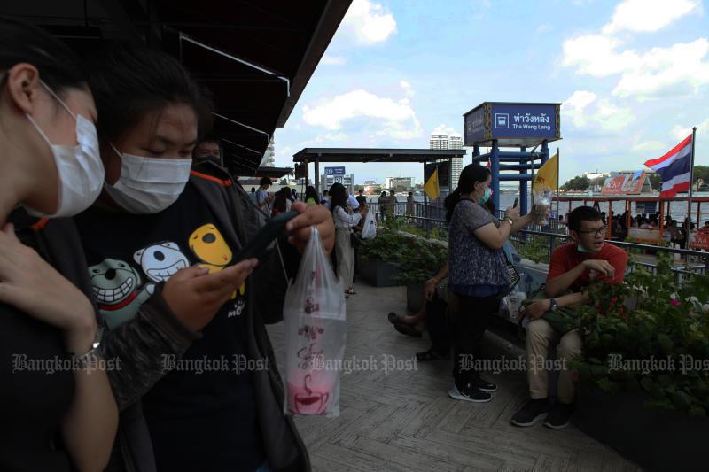Commuters wear face masks while waiting for a boat to cross the Chao Phraya River at Wang Lang pier on Saturday. (Photo: Arnun Chonmahatrakool)