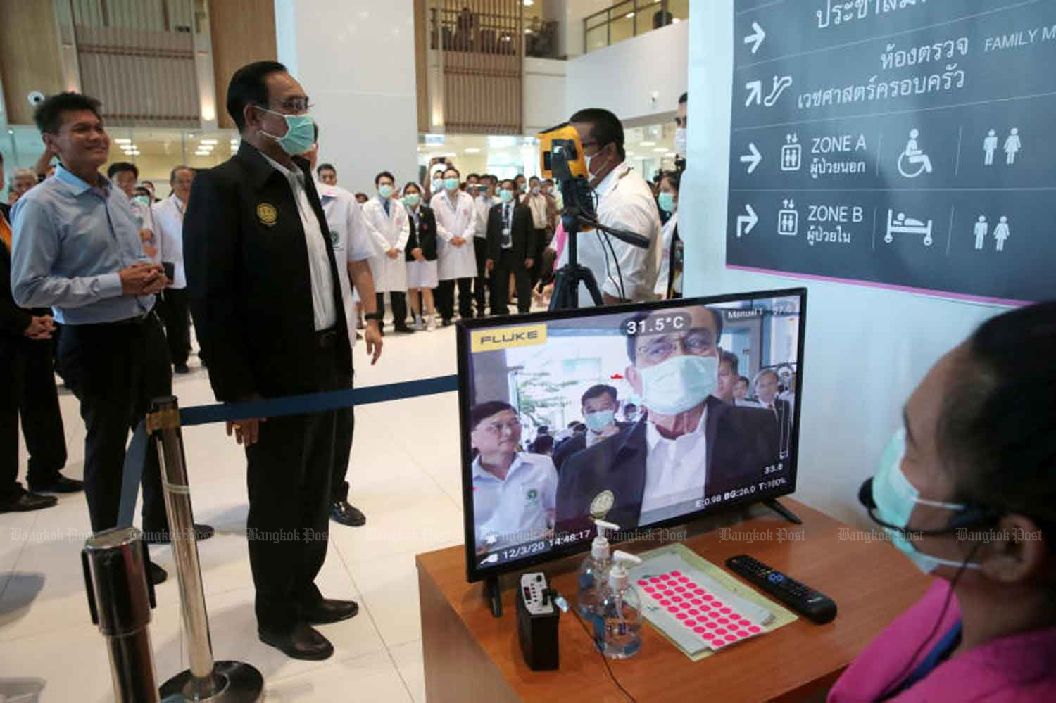Prime Minister Prayut Chan-o-cha, wearing a mask, stands for a thermal scan at Rajavithi Hospital. The premier visited the hospital on Thursday to inspect the health screening process and to give the medical staff some moral support. (Photo: Chanat Katanyu)