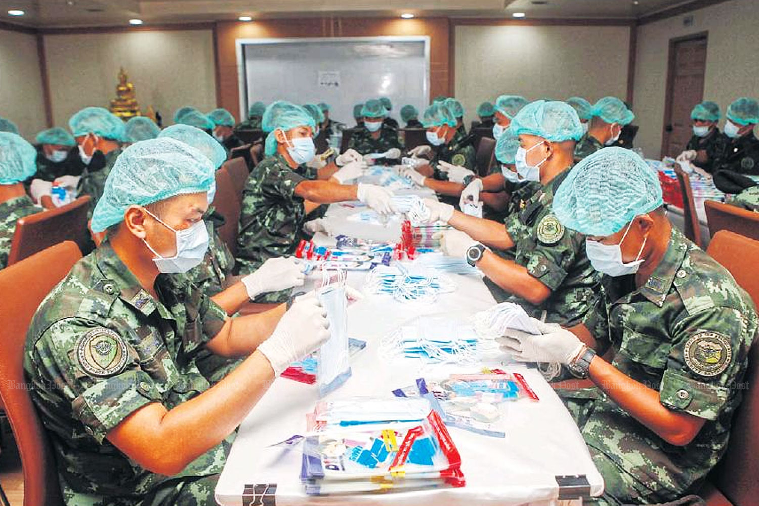 Soldiers pack surgical masks for distribution to hospitals courtrywide as part of a special mission at the Internal Trade Department, which is struggling to deal with a shortage. (Photo by Nutthawat Wicheanbut)