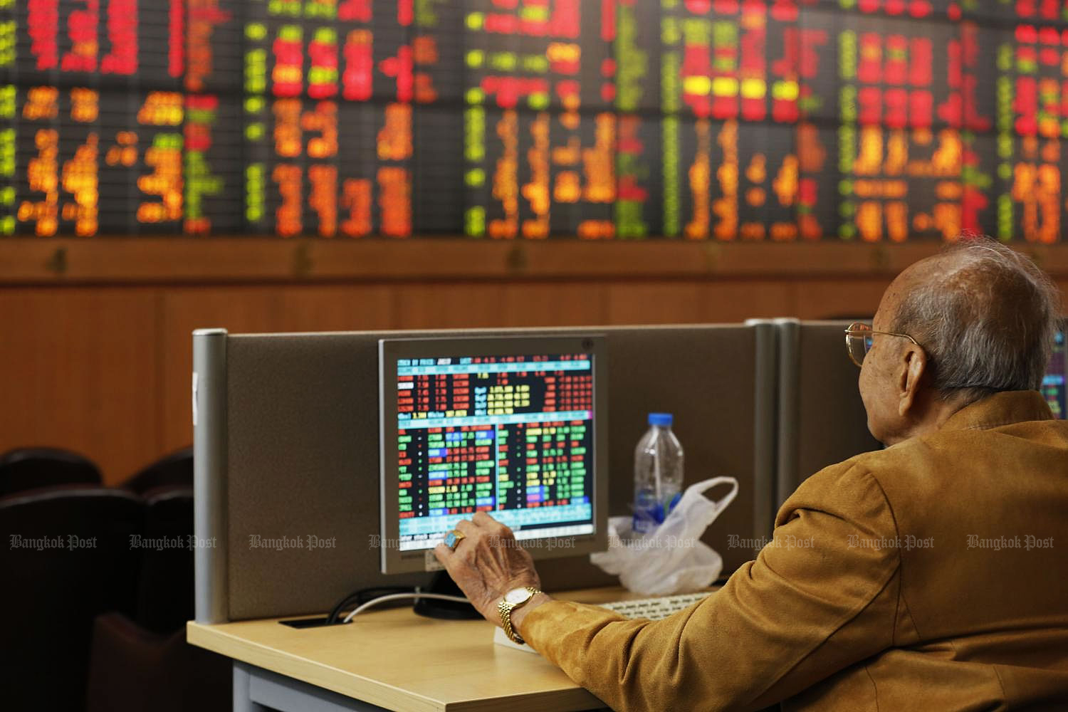 An investor monitors share price movements at Asia Plus Securities' headquarters on Sathon Road.