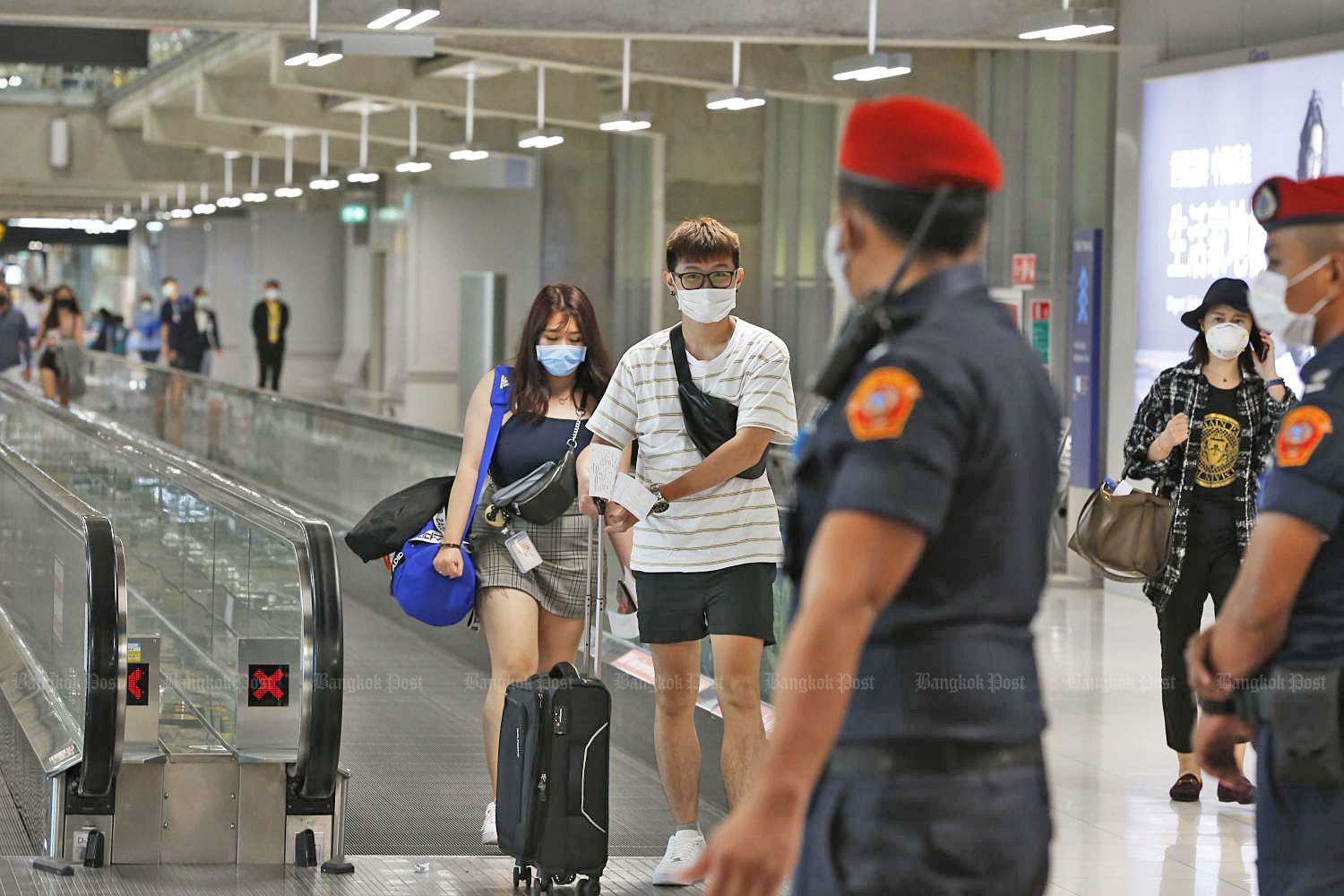 Officials and travellers wear face masks at Suvarnabhumi airport on Thursday.(Photo by Pornprom Satrabhaya)