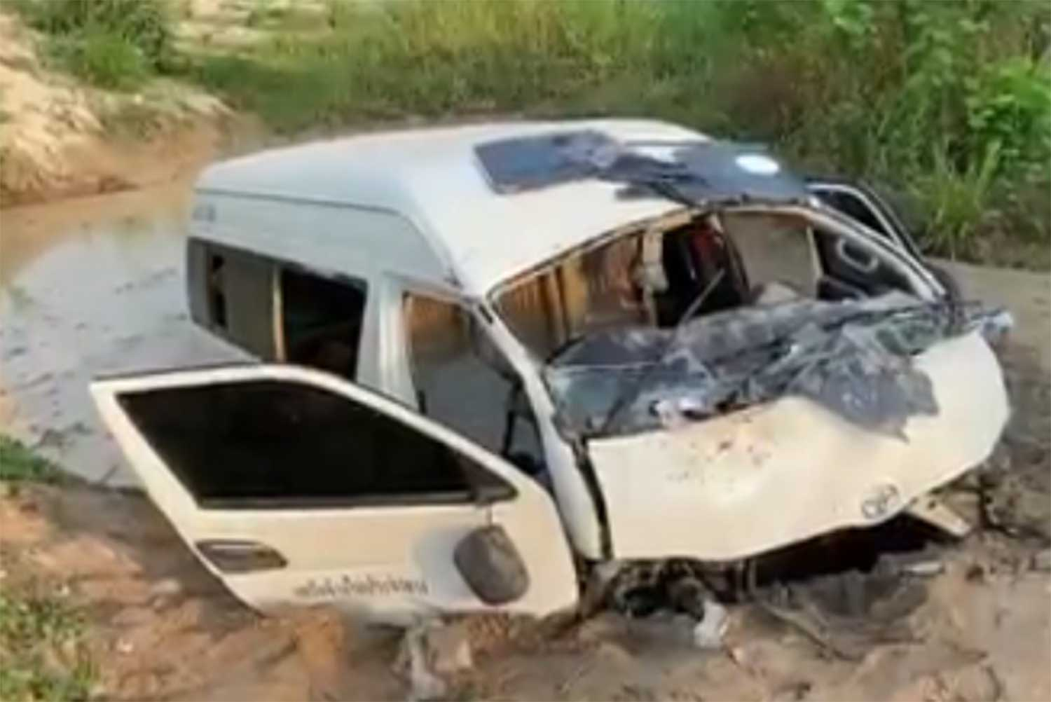 A passenger van rests in a swamp in Nikhom Phatthana district of Rayong, following an accident in which two Cambodian women died. (Screenshot from video clip posted by @ThaiRescueNews2 Facebook page)