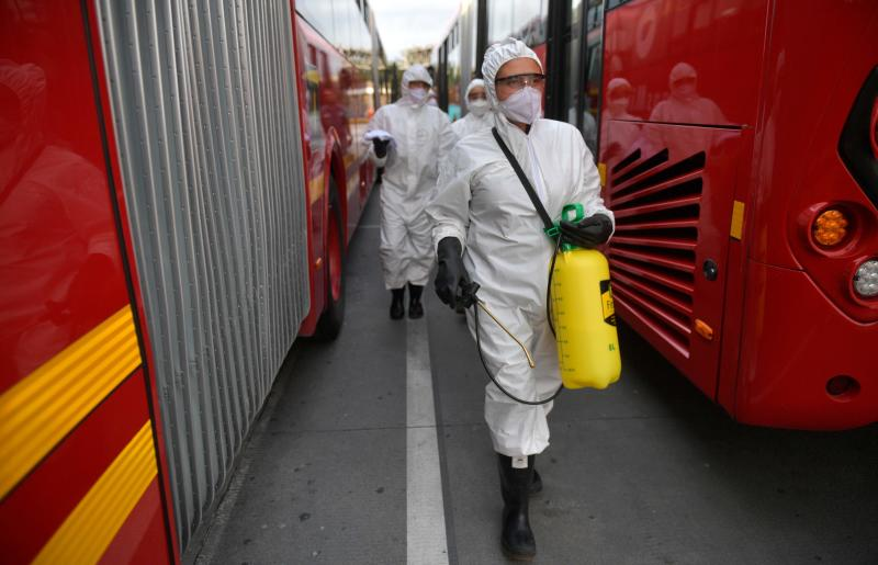 Workers wash and disinfect a bus at the bus station, as a measure to prevent the spread of the new Coronavirus, Covid-19, in Bogota, Colombia, on Sunday. (AFP photo)
