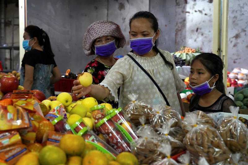 A family wearing protective masks as precaution against coronavirus buys fruits in a market in Phnom Penh on Sunday. (Reuters photo)