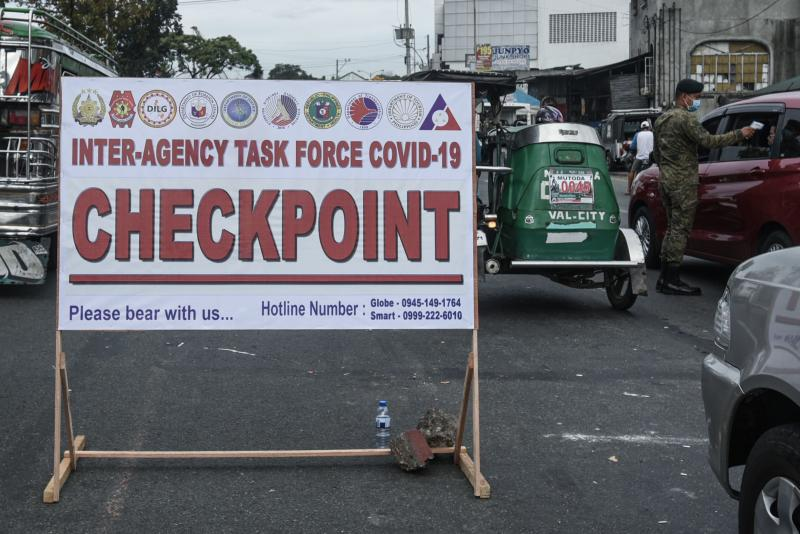 Checkpoint signage is seen as a soldier checks the temperature of a motorist before entering Manila on Monday as part of measures to reduce the spread of the Covid-19 pandemic. (AFP photo)