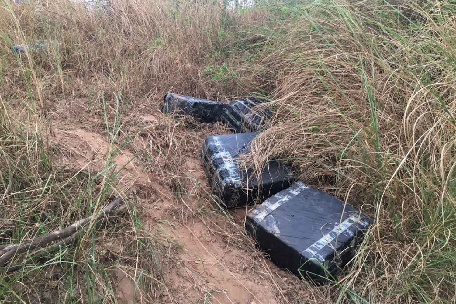 Plastic bags containing 196 kilogrammes of dried marijuana are left on the Mekong river's bank in Wan Yai district of Mukdahan on Tuesday. (Photo: Churoj Triprapakorn)
