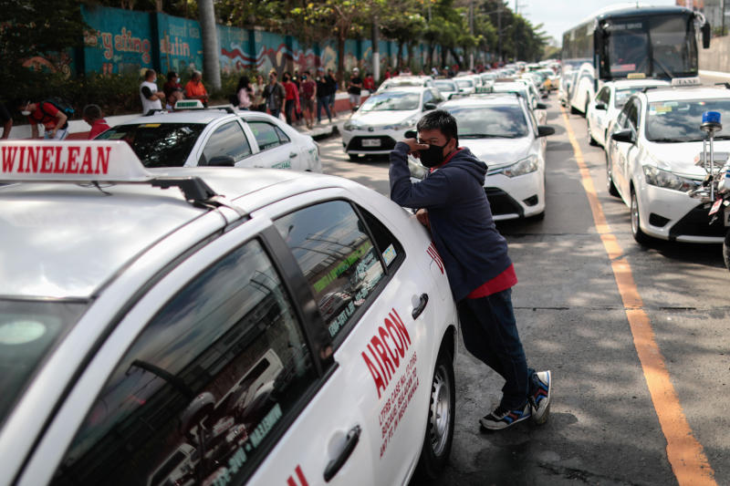 A taxi driver wearing a protective mask stands by his cab after hundreds of them were flagged down by authorities as the government suspends mass transportation to implement an