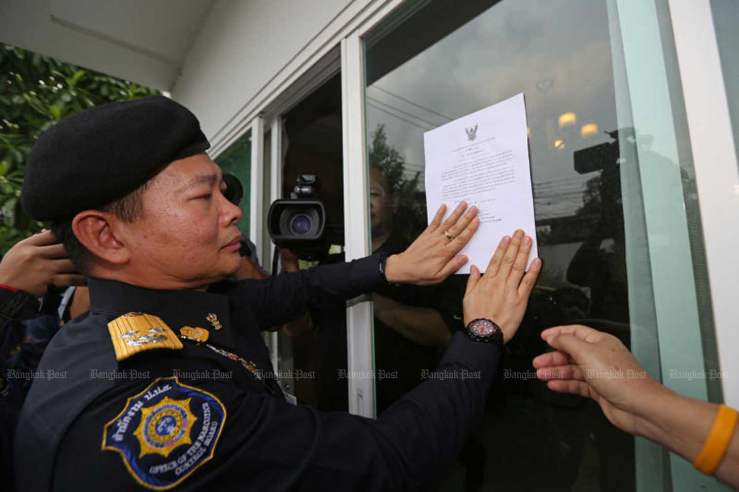 An official document about the seizure of assets from the narcotics ring believed to be run by Chan Xue is placed in front of the door of a house. (Photo by Varuth Hirunyatheb)